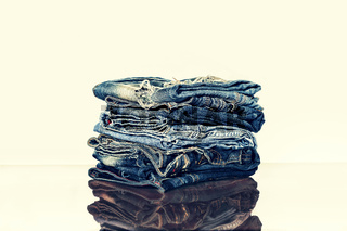 A pile of jeans on the shelf of the store or on the table. Reflection. The concept: the sale in the store