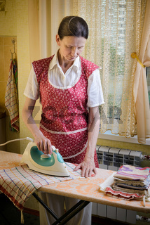Woman Ironing in the Kitchen