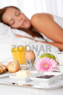 Young woman having breakfast in bed