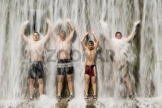 Jungs beim Baden unter dem Wasserfall