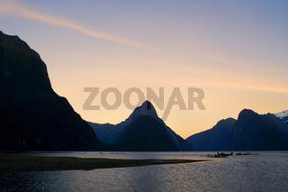 Milford Sound, Wahrzeichen Mitre Peak und umgebende Berge spiegeln sich im ruhigen Wasser des Milford Sound am fruehen Morgen. Milford Sound ist eine der, wenn nicht der, bekanntesten Sehenswuerdigkeiten in Neuseeland,  Fjordland Nationalpark, Suedinsel,