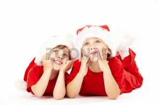 Two small dreaming boys lie in caps of santa
