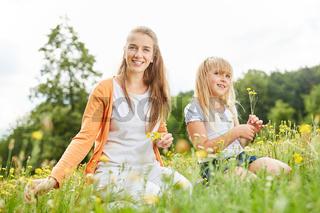 Glückliche Frau als Mutter pflückt Blumen