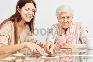 Enkeltochter spielt Domino mit Großmutter