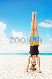 Young woman stand on one's hands on the beach