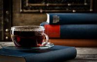 Tasse Tee mit alten Büchern im retro look