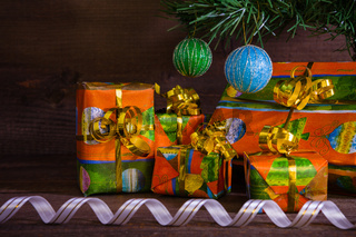 Many Christmas presents under the tree with decorations and ribbon