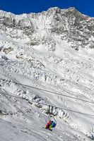 Skifahrer auf einem Sessellift vor dem Feegletscher und dem Dom Gipfel