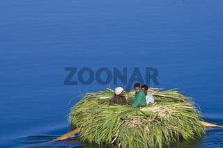 Ägypter befahren mit Schilfboot den Nil
