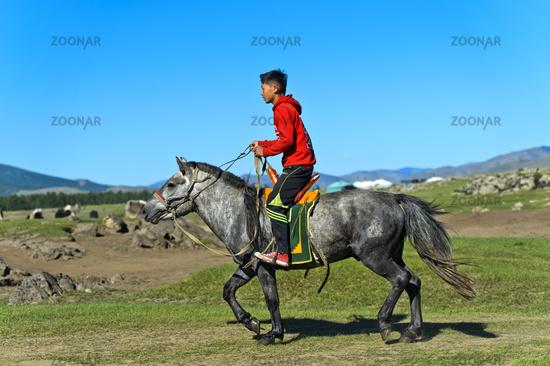 Junge reitet auf einem Pferd durch die Steppe, Mongolei