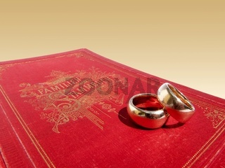 Sehr altes rotes Familienstammbuch mit zwei goldenen Eheringen