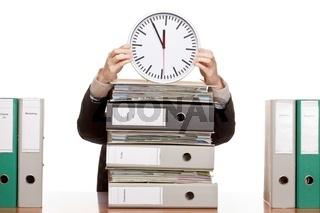 Frau im Büro mit Aktenstapeln hat starken Zeitdruck