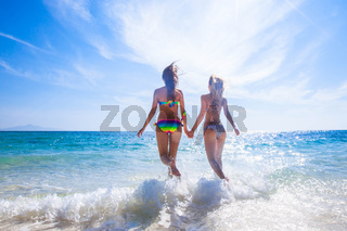 Two women running by the beach