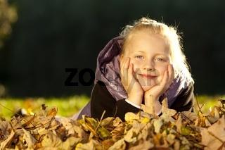 Junges glückliches Mädchen liegt am Boden im Herbstlaub
