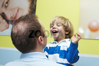 Kleiner Junge lacht mit seinem Vater