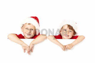 Two little boys in caps of santa lean against the blank banner isolated