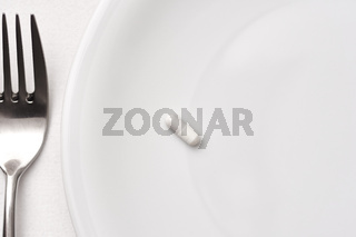 Gabel und Kapsel auf einem Teller