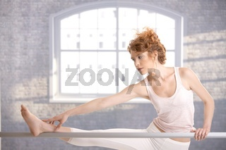 Ballerina girl practicing by bar touching her foot