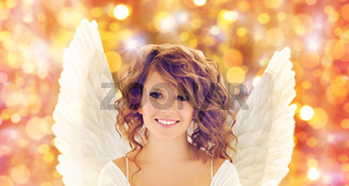 happy young woman or teen girl with angel wings