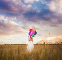 girl holds balloons