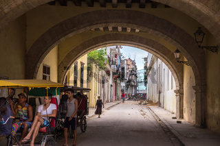 Streetscene of Cuban people in bicycle taxi in old Havana