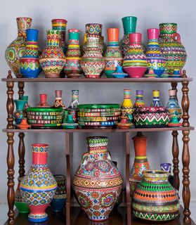 Colorful painted pottery vases stacked in wooden storage shelves