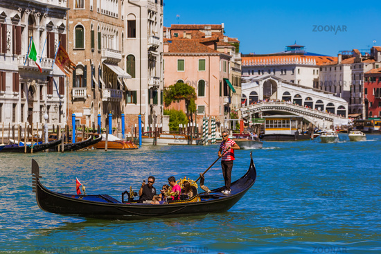 VENICE, ITALY - AUGUST 22, 2016: Tourists ride in gondola near Rialto bridge on August 22, 2016 in Venice Italy