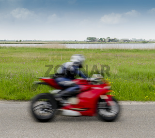 Fast Red Motorcyclist on Dike