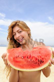 Sommer: Frau isst Wassermelone am Strand