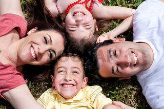 Happy family laying in the circle on green grass