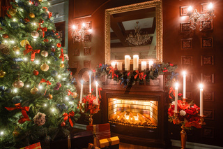 Christmas evening by candlelight. classic apartments with a white fireplace, decorated tree, sofa, large windows and chandelier.