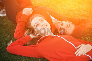 Sport man and woman resting in park