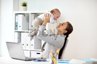 happy businesswoman with baby and laptop at office