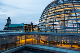 Illuminated glass dome on the roof of the Reichstag in Berlin at dusk.