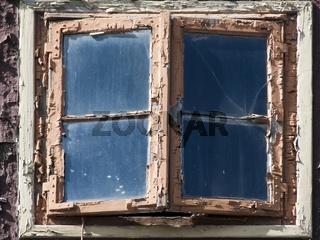 Altes Fenster mit abblaetternder Farbe in einem Fachwerkhaus