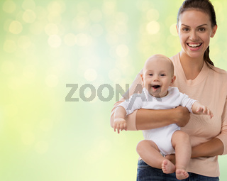 happy mother with little baby boy over lights