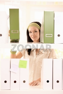 Pretty office girl arranging folders