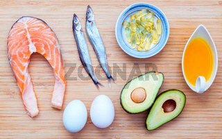 Selection food sources of omega 3 and unsaturated fats. Super food high vitamin e and dietary fiber for healthy food. Olive oil ,white eggs ,fish oil ,avocado ,shishamo fish and salmon on bamboo cutting board.
