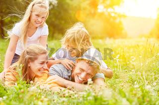 Familie liegt im Sommer auf Wiese im Urlaub