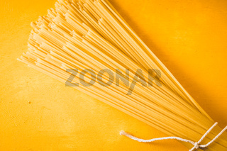 Raw spaghetti on the yellow background top view