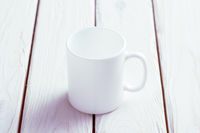 White cup mock-up on wooden table