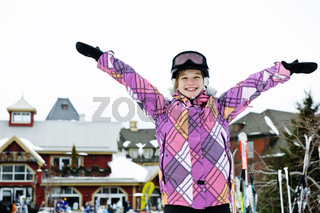 Happy girl with arms raised at resort