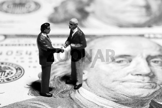 Miniature figurines of two discussing businessmen