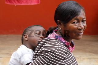 Frau mit Kind auf dem Rücken