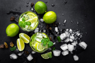 Refreshing mint cocktail mojito with rum and lime, cold drink or beverage with ice on black background, top view