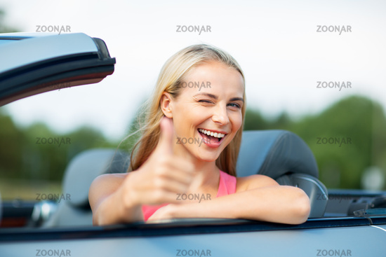 happy young woman in convertible car thumbs up