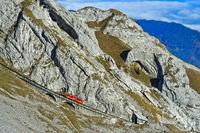 Roter Wagen der Pilatusbahn auf der steilen Bahnstrecke am Pilatus Bergmassiv, Schweiz