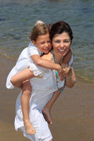 Mother carrying daughter on beach