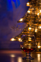 One cognac glass on the background of a New Year tree