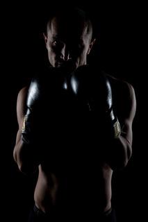 Foto eines kraftvollen Mannes bei Dunkelheit
